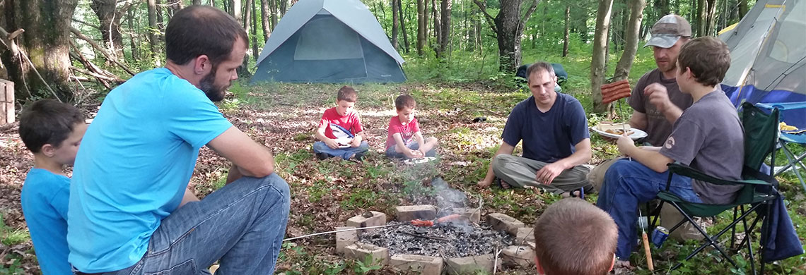 Father son campout around fire